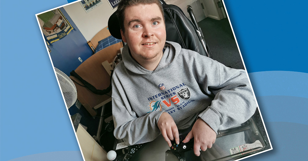 Smiling young man in wheelchair holding modified controller